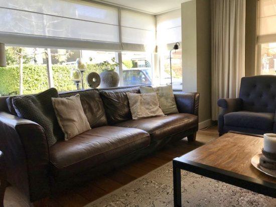 Landelijke woonkamer met leren bank en vouwgordijn