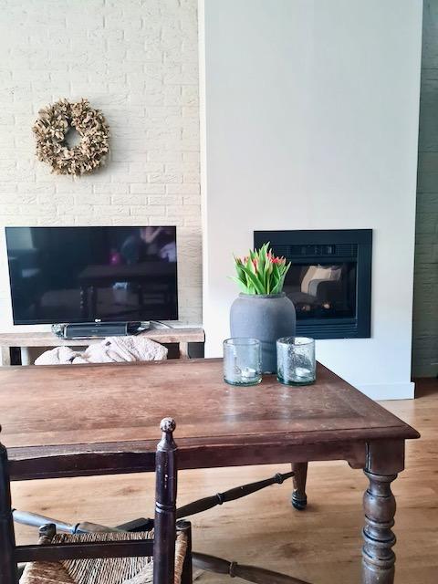 Strakke haard houten salontafel kruik met tulpen krans muur
