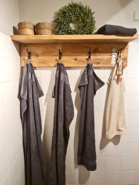 Houten kapstok met handdoeken krans en rieten mandjes