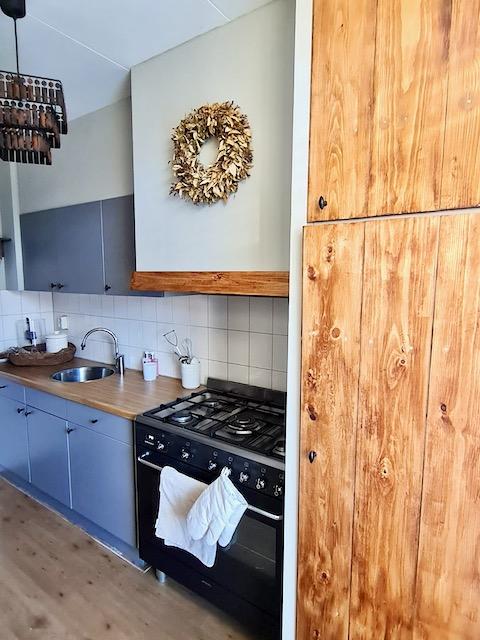 Houten kast blauwgrijze landelijke keuken krans schouw