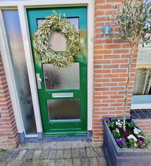 Groene voordeur met groene krans