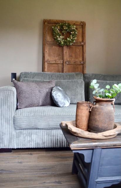 Grijze ribcord bank rond grijs kussen houten bak salontafel