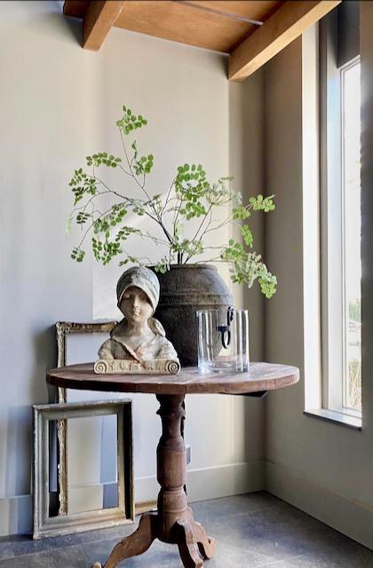 Wijntafel hal beeld vrouw grote landelijke kruik met groen glazen windlicht met hangkandelaar