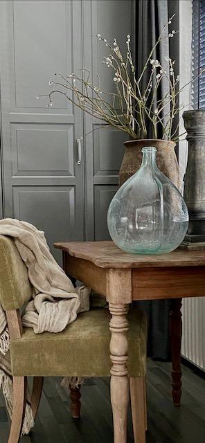 Oud tafeltje groen oud stoeltje glazen fles kruik met takken