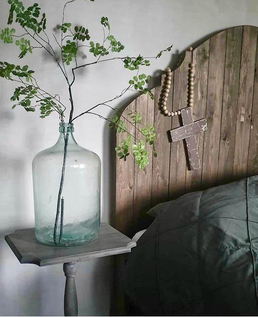 Glazen fles met kunstbloem op wijntafel naast houten bed kruis woonketting
