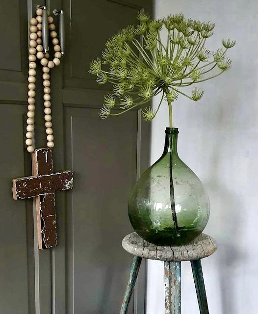 Houten kruis aan woon ketting groene fles met kunst berenklauw op kruk